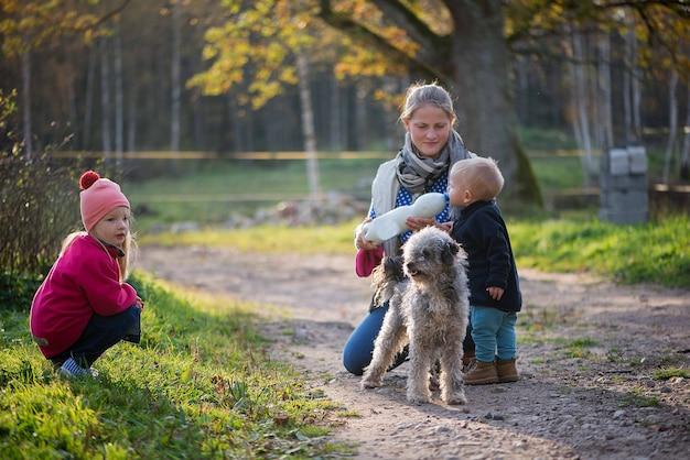 Madre di famiglia felice e due bambini ragazza e ragazzo che giocano con il cane all'aperto