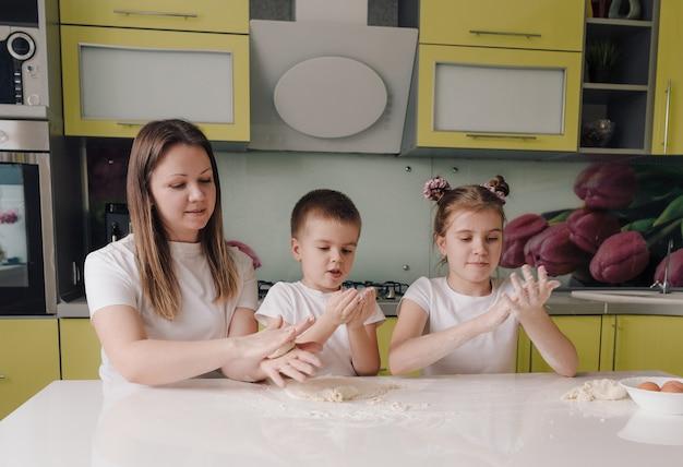 Famiglia felice una madre e due bambini piccoli imparano a fare la pasta in una cucina domestica