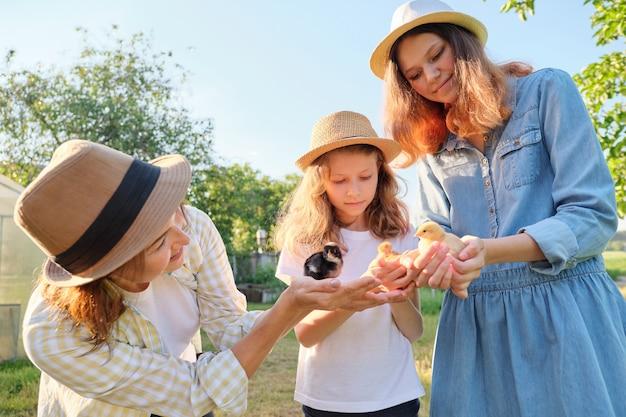 Madre di famiglia felice con la figlia in natura, donna che tiene piccoli pulcini neonato nelle mani