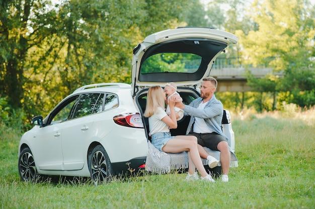 Famiglia felice vicino al bagagliaio dell'auto in giornata di sole. viaggio su strada