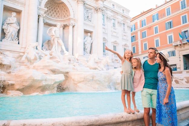 Famiglia felice vicino a fontana di trevi con la mappa della città