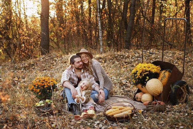 Famiglia felice su un picnic con le zucche in autunno