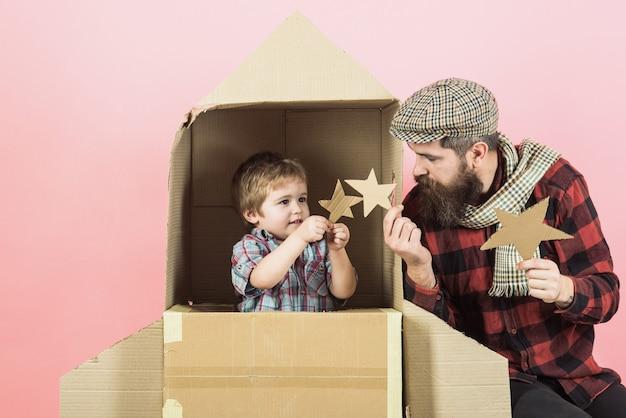 La famiglia felice gioca con il razzo di cartone. padre e figlio tengono in mano le stelle. il ragazzo è seduto in un razzo spaziale di cartone. infanzia, concetto di genitorialità - il bambino con il padre gioca all'astronauta. i sogni dei bambini