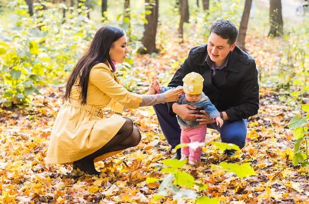 Famiglia felice che gioca contro il fondo vago delle foglie gialle nella sosta di autunno