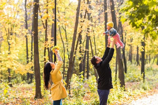 Famiglia felice che gioca contro foglie gialle sfocate