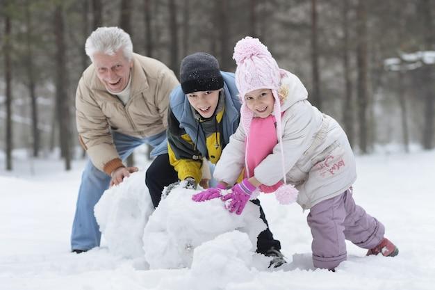 Famiglia felice che gioca nella neve fresca e nel pupazzo di neve in una bella giornata invernale di sole all'aperto nella natura