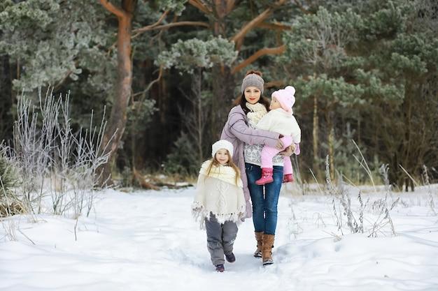 Famiglia felice che gioca e ride in inverno all'aperto nella neve. giornata invernale del parco cittadino.