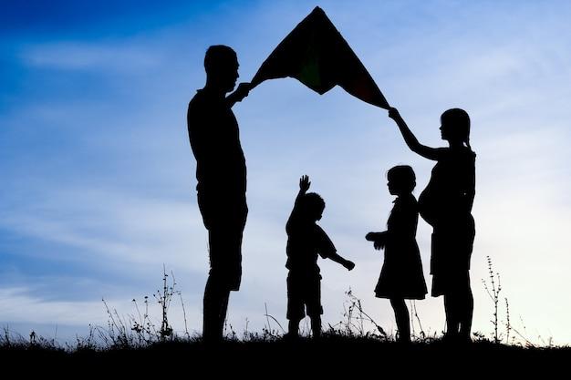 Famiglia felice che gioca sulla siluetta di estate della natura