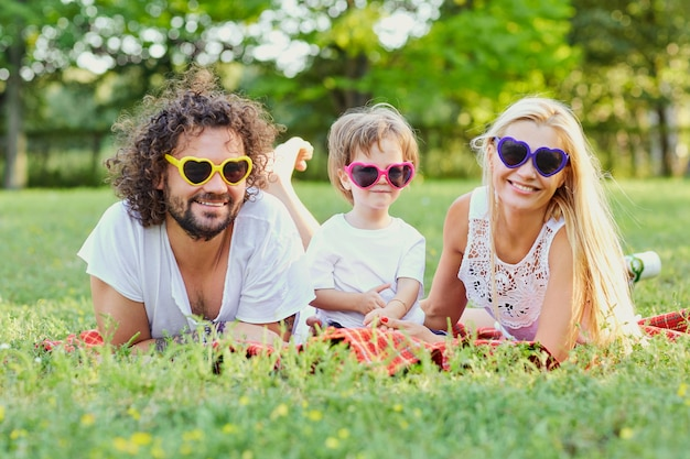 Famiglia felice che gioca nel parco. madre, padre e figlio giocano insieme nella natura in estate, in primavera.
