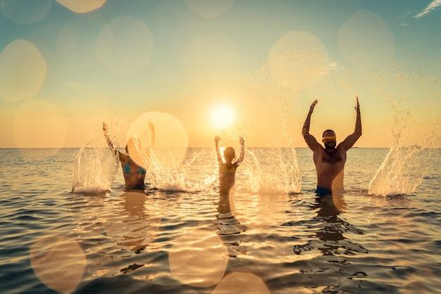 Famiglia felice che gioca nel mare persone che si divertono all'aperto vacanze estive e concetto di stile di vita sano