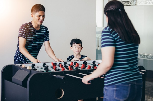 La famiglia felice che gioca calcio-balilla per si rilassa in vacanza nella casa