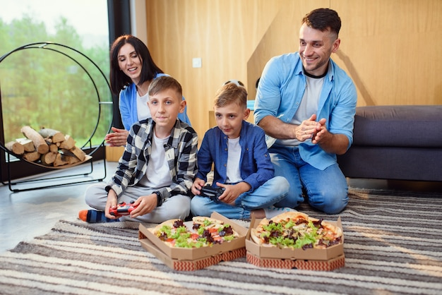 Famiglia felice che gioca ai videogiochi con gamepad e mangia una gustosa pizza