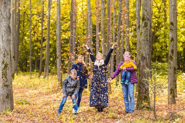 Famiglia felice che gioca con le foglie di autunno nel parco