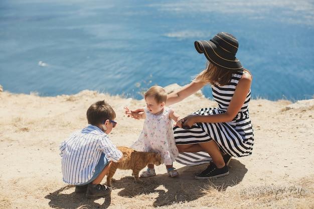 Famiglia felice che gioca con un gatto in natura.