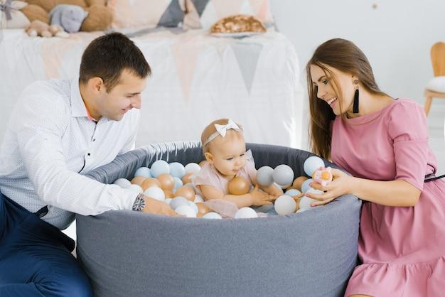 Famiglia felice che gioca con palloncini colorati nella stanza dei bambini a casa