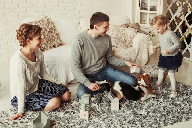 Famiglia felice che gioca con un cane nell'ampio soggiorno