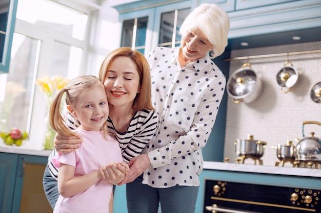 Famiglia felice. piacevole bambina in piedi in cucina e abbracciata dalla madre e dalla nonna mentre le tre femmine si uniscono