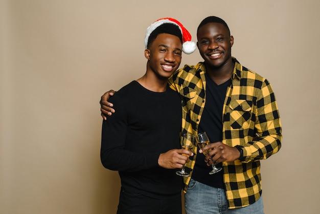 Ritratto di famiglia felice a natale, coppia gay maschile su sfondo beige. un paio di uomini neri innamorati tintinnano bicchieri di champagne. saluti. festeggia natale e capodanno.