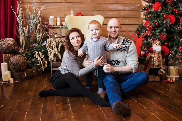 Felice ritratto di famiglia a natale, madre, padre e figlio seduti sul seggiolone a casa, decorazioni natalizie e regali intorno a loro