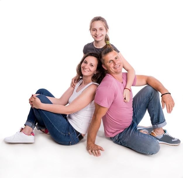 Famiglia felice in posa su un muro bianco