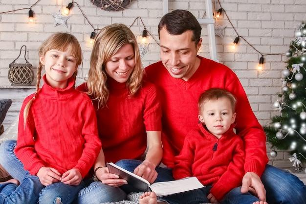 Famiglia felice che legge un libro a casa a natale