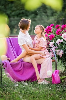 Rapporti familiari felici. mamma e figlia si siedono su una panchina e chiacchierano in giardino tra i fiori in una soleggiata sera d'estate.