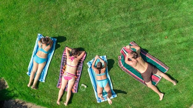 La famiglia felice che si distende dalla piscina, vista aerea del drone dall'alto di genitori e bambini si divertono in vacanza