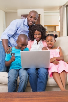 Famiglia felice che si distende sul divano che compera online
