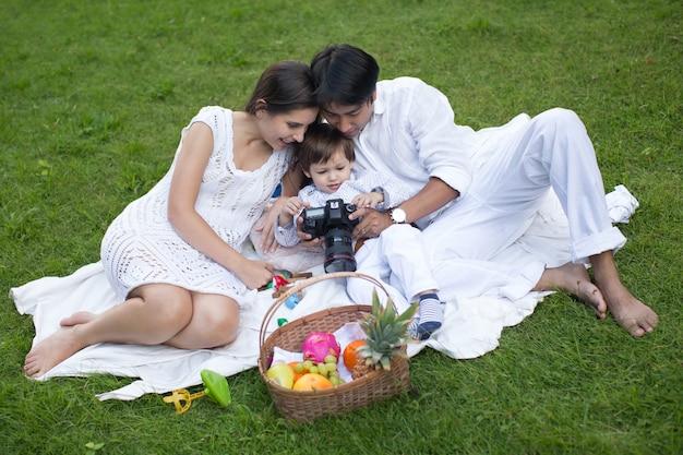 Famiglia felice che si distende al parco in una bella giornata estiva.
