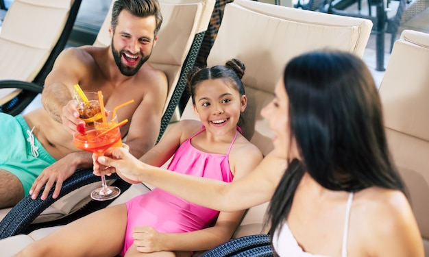 Famiglia felice nel resort. bel padre, bella madre e loro piccola figlia carina sono sdraiati sui lettini nel grande centro termale con piscina e bevande succhi e cocktail
