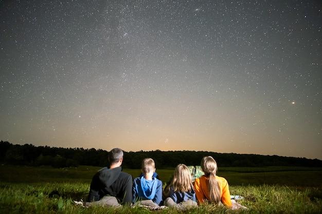 Famiglia felice che riposa nel campo di notte guardando il cielo scuro con molte stelle luminose. genitori e figli che osservano la pioggia di meteoriti.
