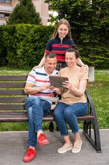 Famiglia felice che riposa nel parco e utilizza tablet pc all'aperto nel parco