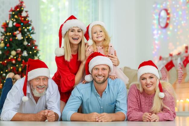 Famiglia felice in cappelli di babbo natale che celebra il natale a casa