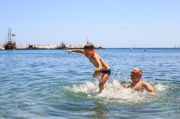 Famiglia felice in un mare divertendosi e spruzzi d'acqua in estate