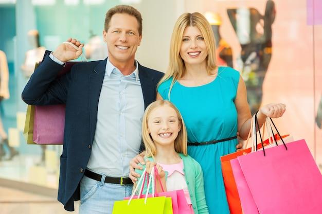 Acquisto felice della famiglia. famiglia allegra che tiene le borse della spesa e sorride alla macchina fotografica mentre sta in piedi nel centro commerciale