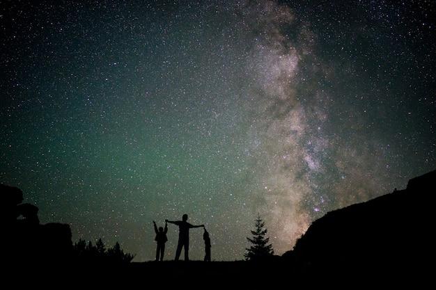 Siluetta felice della famiglia con la via lattea e bello cielo notturno pieno di stelle sullo sfondo