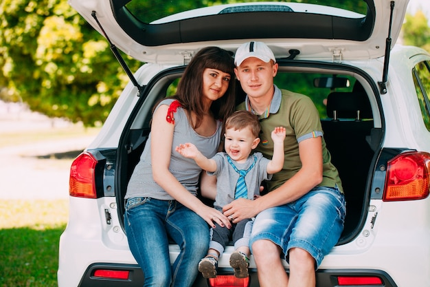 Famiglia felice che si siede in macchina