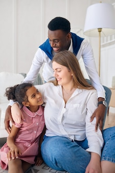 Famiglia felice seduta sul pavimento in soggiorno