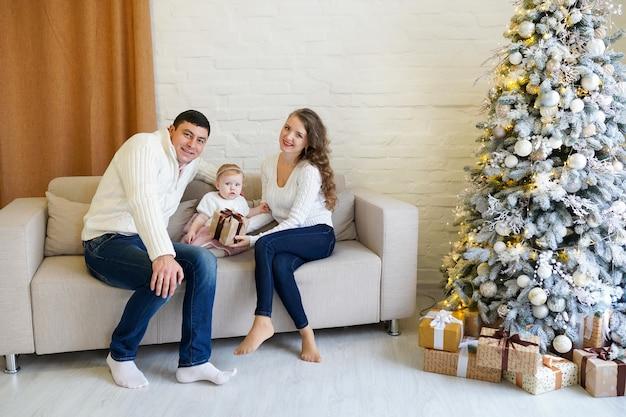 Famiglia felice che si siede sul divano e festeggia il nuovo anno vicino all'albero di natale