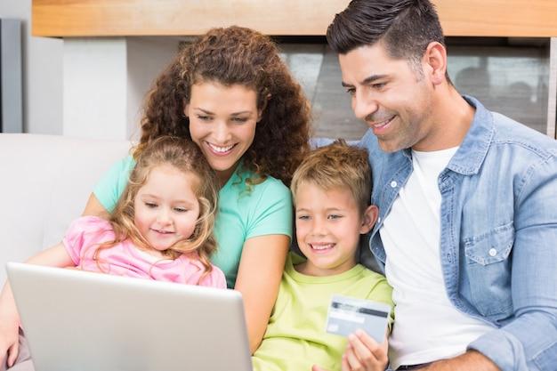 Famiglia felice che si siede insieme sul sofà per mezzo del computer portatile da acquistare in linea