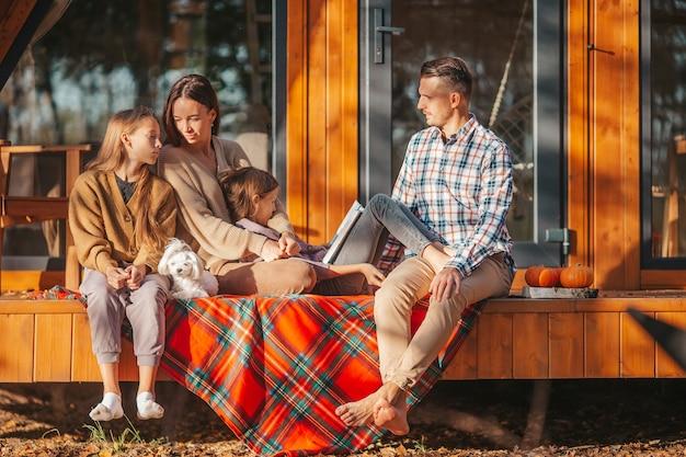 Famiglia felice che si siede sulla terrazza della loro casa in autunno