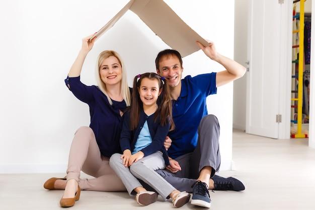 Famiglia felice seduta insieme e facendo il segno di casa