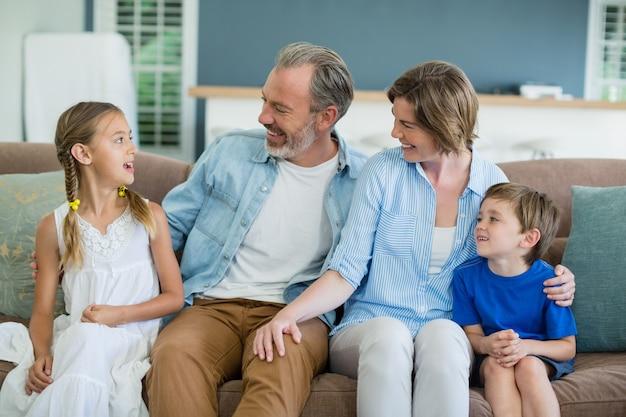 Famiglia felice che si siedono insieme sul divano nel soggiorno