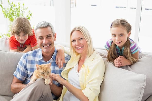 Famiglia felice che si siede con il gatto sul sofà a casa