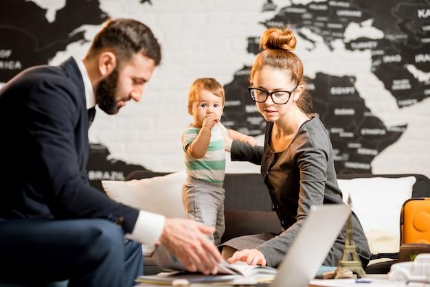 Famiglia felice seduta con l'agente uomo presso l'ufficio dell'agenzia di viaggi con una bella mappa sullo sfondo che sceglie un tour per una vacanza estiva