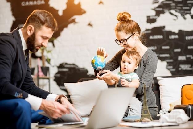 Famiglia felice seduta con l'agente uomo presso l'ufficio dell'agenzia di viaggi con una bella mappa sullo sfondo che gioca con un globo