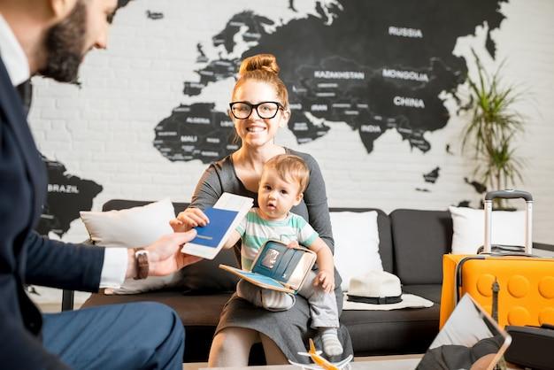 Famiglia felice seduta con l'agente uomo presso l'ufficio dell'agenzia di viaggi con una bella mappa sullo sfondo che riceve biglietti e passaporto per una vacanza estiva