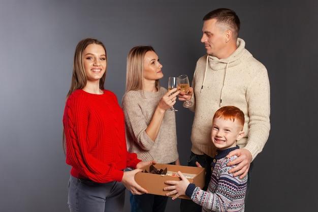 La famiglia felice sorride, celebra la vacanza nello studio fotografico su uno sfondo grigio