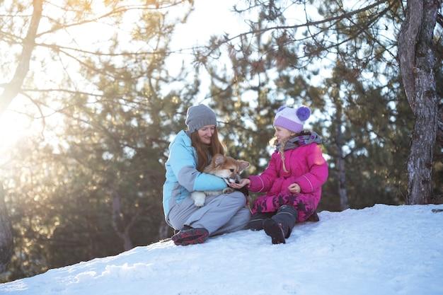 Famiglia felice - madre e figlia sorridenti con un piccolo cucciolo lanuginoso di corgi al giorno d'inverno