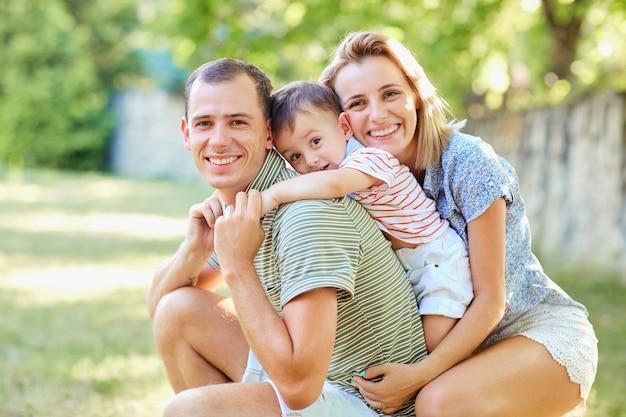 Famiglia felice che sorride giocando nel parco estivo.